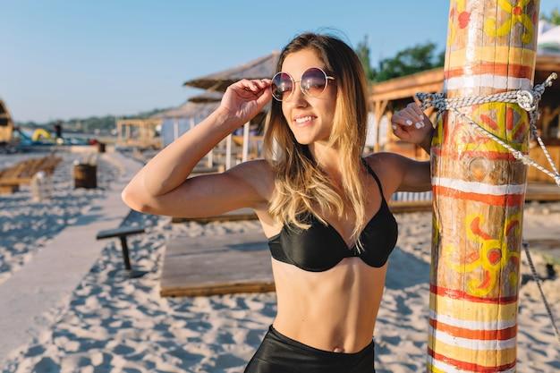 Attraente donna moderna vestita in costume da bagno nero sulla spiaggia estiva