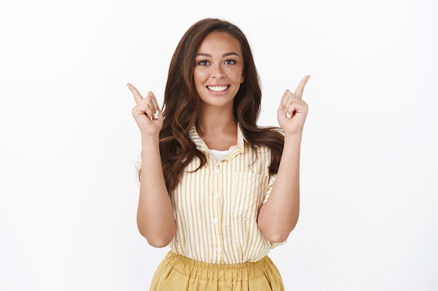 Attractive modest caucasian brunette, girl smiling toothy and upbeat, raising hands, pointing up, introduce good offer, suggest try-out product, indicate copy space, recommend awesome service