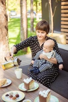 ヨーロッパの夏の屋外カフェで小さな赤ちゃんを持つ魅力的なママ