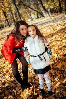 Привлекательная мать и ее счастливая маленькая дочь гуляют вместе в осеннем парке