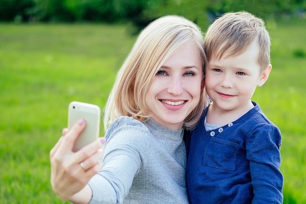 Привлекательная мама и любимый сын фотографируют селфи на телефон в парке на фоне зеленой травы и деревьев.