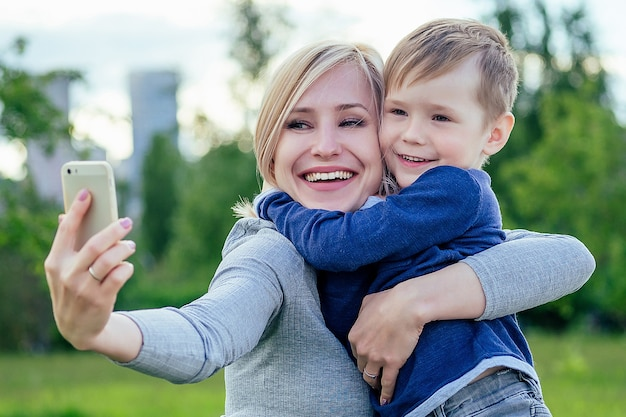 魅力的な母親の女性と小さな男の子は、緑の草や木々を背景に公園で電話で自分撮りをします。息子はお母さんを抱きしめます。