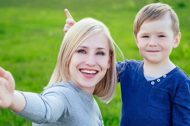 Привлекательная мать (лицо женского пола) и маленький мальчик фотографируют селфи на телефон в парке на фоне зеленой травы и деревьев