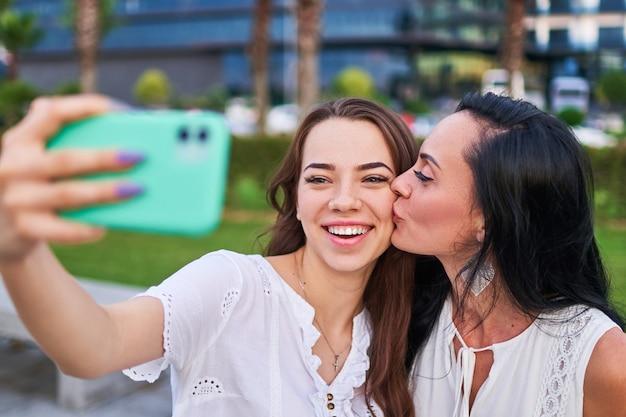 Привлекательная мать целует в щеку свою радостную счастливую дочь и делает селфи-фотопортрет на камеру телефона во время прогулки на свежем воздухе