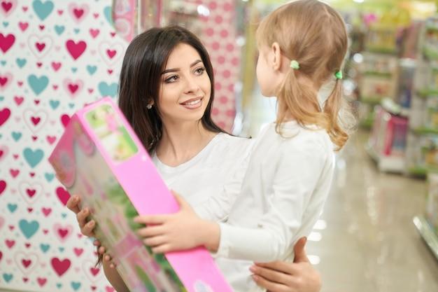 Madre attraente che presenta nuovo giocattolo alla figlia