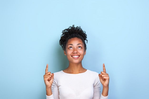 Attractive mulatto woman pointing by her both index fingers up to place for copy space