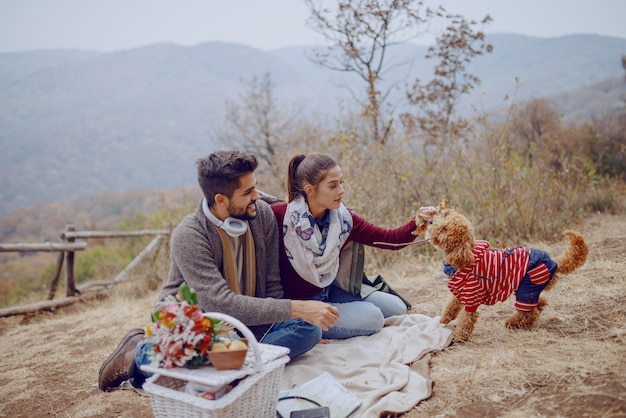 Attractive multicultural couple sitting on blanket and playing with their dog. picnic at autumn concept.