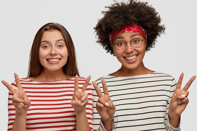 Le giovani donne femminili multietniche attraenti indossano abiti a righe, mostrano il segno v con entrambe le mani, sorridono ampiamente, hanno sorrisi a trentadue denti, isolate su un muro bianco, dimostrano il gesto di vittoria.
