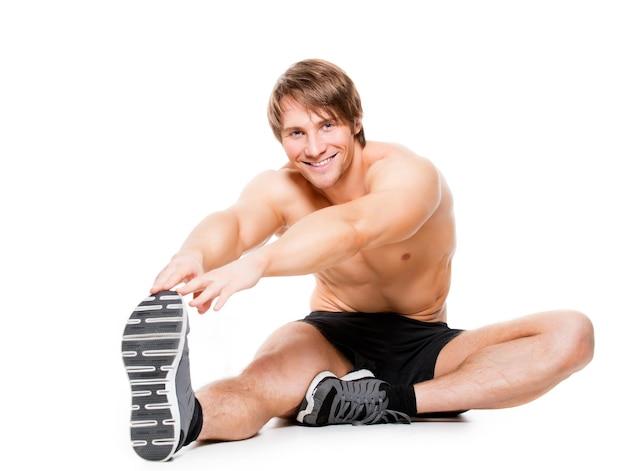 Attraente uomo muscoloso che si estende su un pavimento - isolato su bianco.