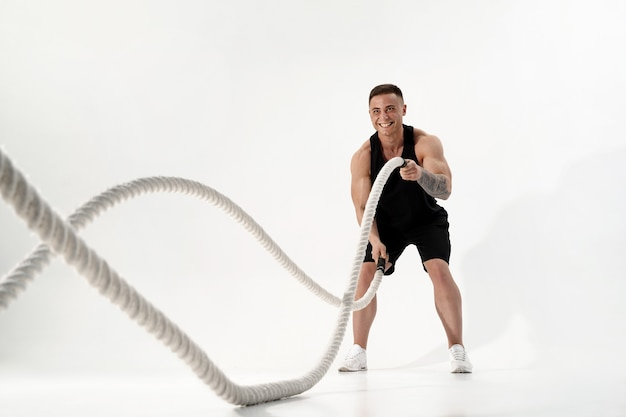 Attractive muscular man working out with heavy ropes. photo of handsome man in sportswear isolated on white . crossfit