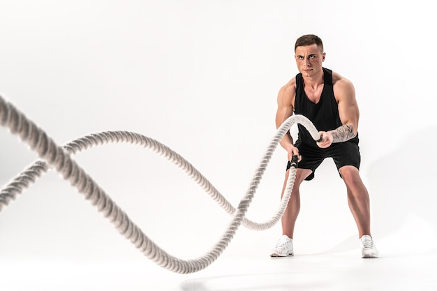 Attractive muscular man working out with heavy ropes. photo of handsome man in sportswear isolated on white wall. crossfit