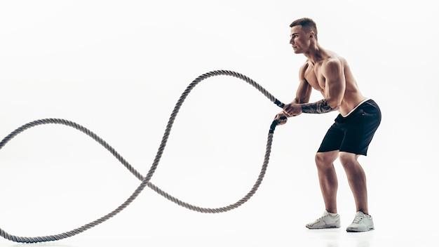 무거운 로프와 함께 밖으로 작동하는 매력적인 근육 질의 남자. 흰 벽에 고립 된 운동복에 잘 생긴 남자의 사진. 크로스 핏