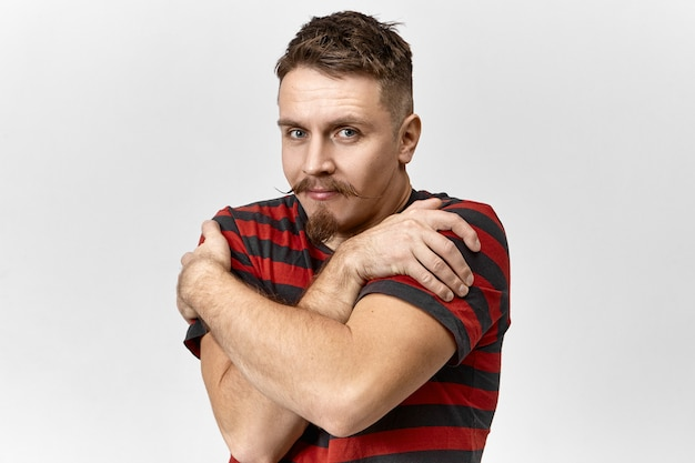 Attractive muscular young bearded male wearing striped t-shirt crossing arms on his chest, keeping hands on shoulders as if feeling cold. handsome guy with mustache embracing himself in studio