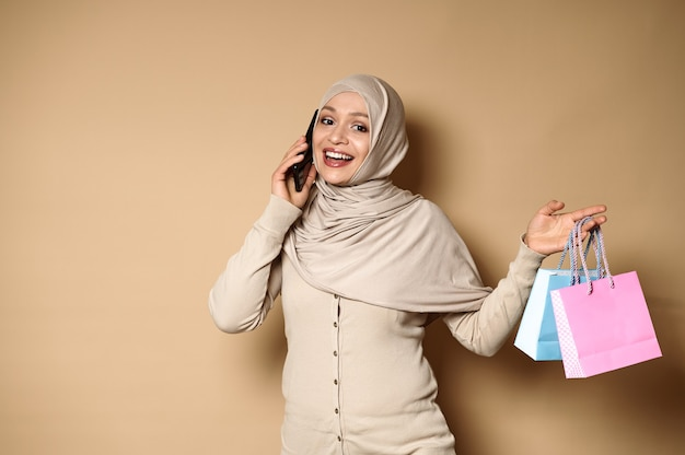カラーの紙袋を持って携帯電話で話しているヒジャーブで美しい笑顔を持つ魅力的なイスラム教徒のアラブの女性。