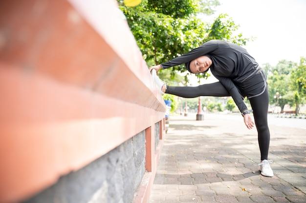 魅力的なイスラム教徒のアジアの女性は晴れた日の屋外スポーツ時間中に彼女の足を伸ばす