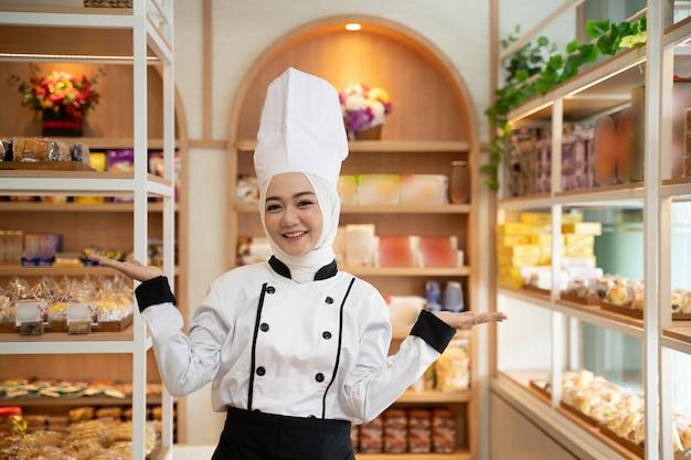 彼女の店に立っている間カメラに微笑んでいる魅力的なイスラム教徒のベイカー