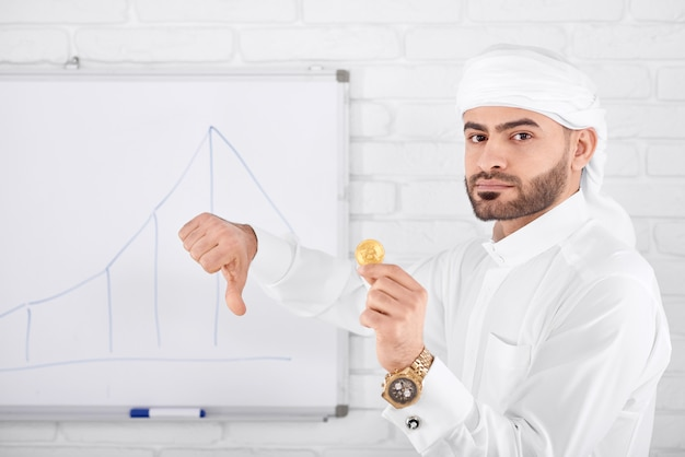 Attractive muslim being serious holding golden bitcoin and showing thumbs down
