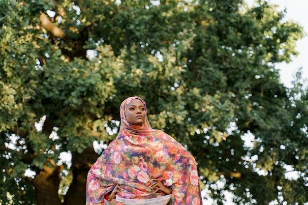매력적인 이슬람 흑인 소녀가 hijab 미소를 지으며 오른쪽으로 보입니다.