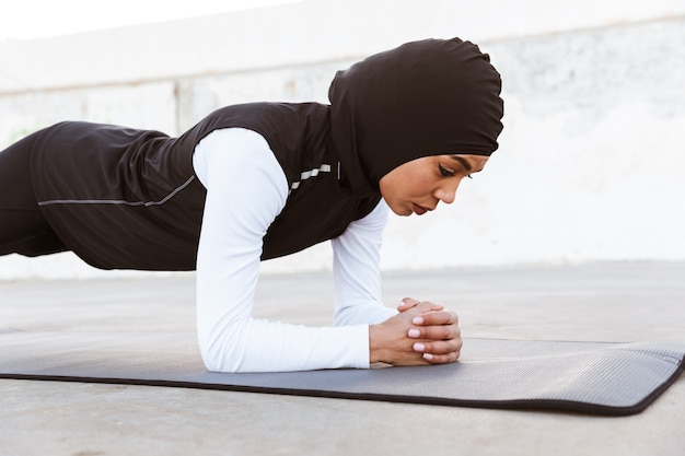 Attractive muslim sportswoman wearing hijab outdoors, doing plank exercises on a fitness mat