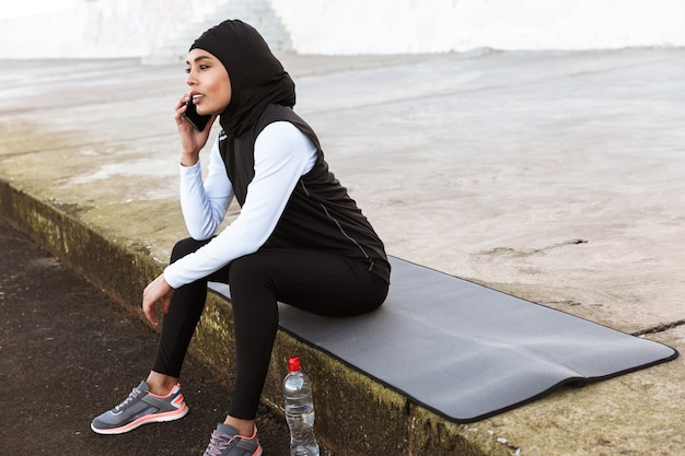 Attractive muslim sportswoman wearing hijab outdoors, sitting on a fitness mat, taking on mobile phone