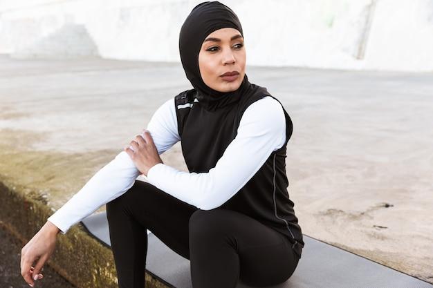 야외에서 히잡을 쓰고 피트니스 매트에 앉아 있는 매력적인 이슬람 운동가