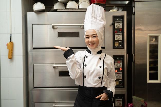 大きなオーブンでパン屋のキッチンでカメラに微笑んで魅力的なイスラム教徒の女性ベイカー