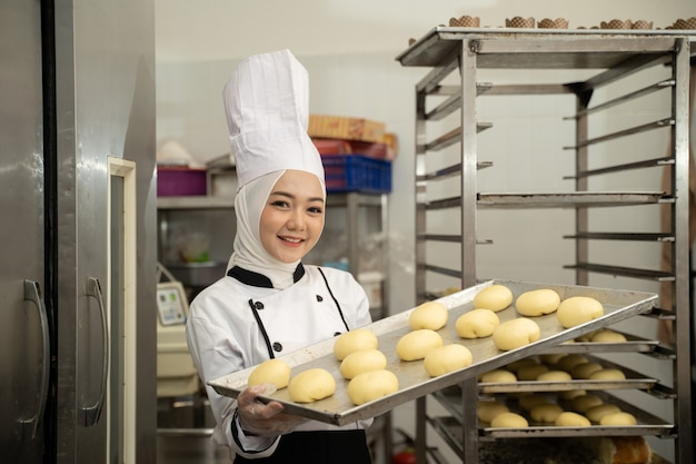 Attractive muslim woman chef profession holding tray smiling to camera wear hijab