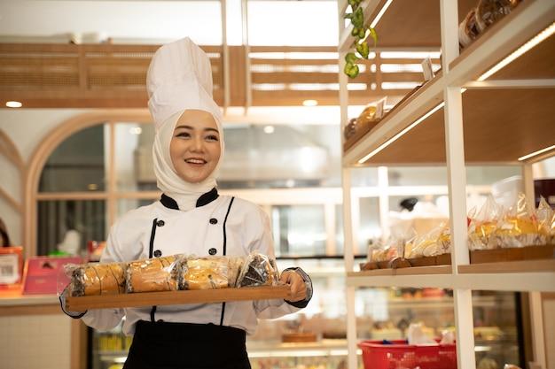 カメラウェアヒジャーブに微笑んでトレイを保持している魅力的なイスラム教徒の女性シェフの職業