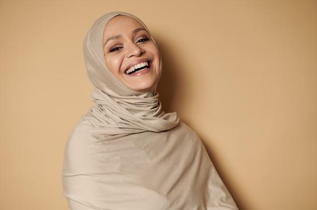 ヒジャーブの魅力的なイスラム教徒の女性、コピースペースでベージュに対してカメラを見て笑う