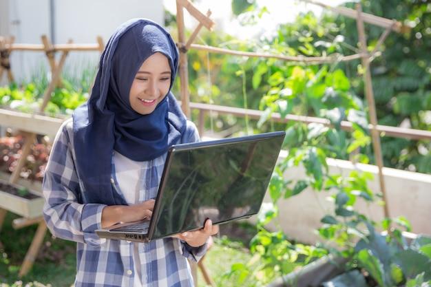 Привлекательная мусульманская женщина с ноутбуком в ферме