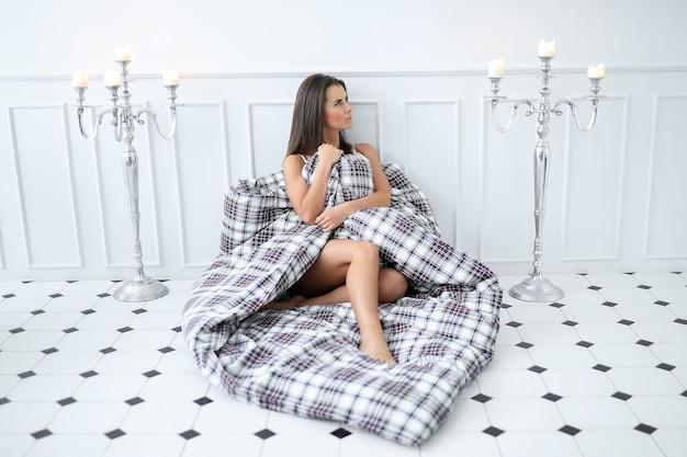 이불로 자신을 덮고 침대에서 매력적인 벌거 벗은 여자