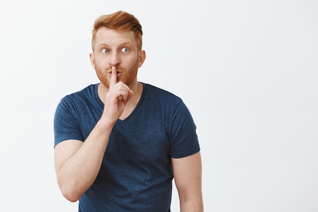 Attractive nervous redhead guy with beard, bending towards showing shh gesture, saying shush with index finger over mouth, staring right anxiously, keeping secret, telling rumors