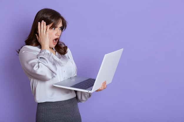 Attractive nervous young business woman with laptop in hands, looking at screen of device with shocked expression, touching her head with hand, keeps mouth widely opened, stands against lilac wall.