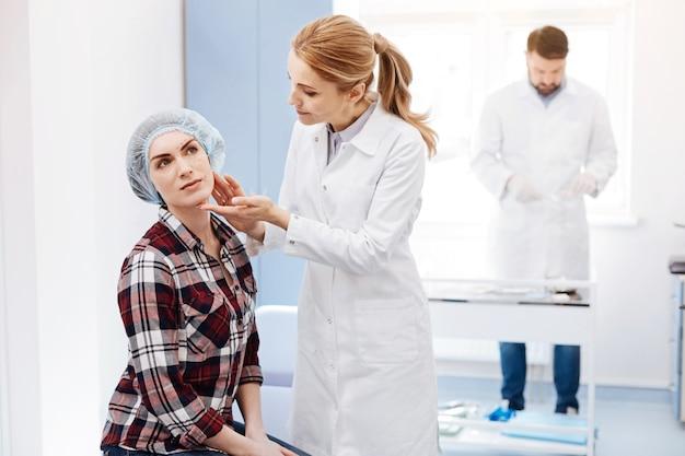 매력적인 좋은 젊은 여자가 그녀의 의사 앞에 앉아 그녀에 의해 검사되는 동안 그녀의 머리를 돌려