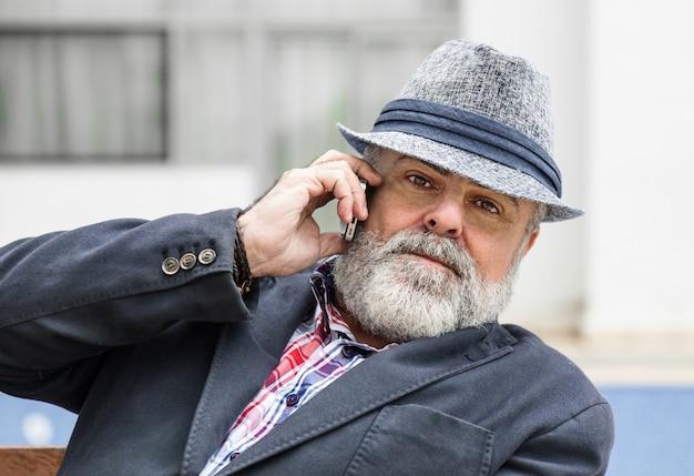수염과 모자 전화 통화와 매력적인 노인