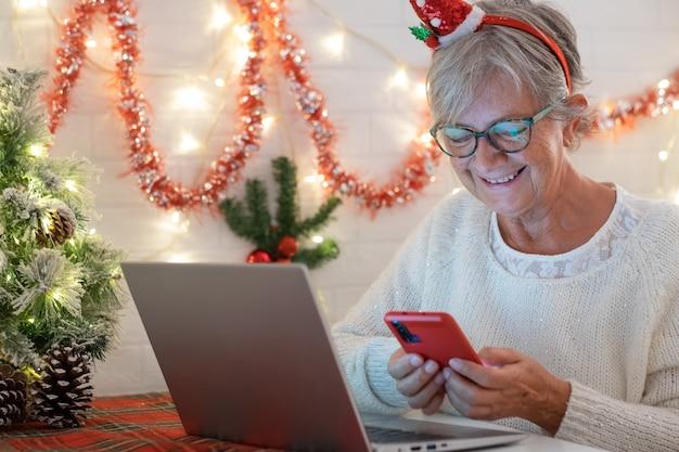 Привлекательная старая старшая женщина, использующая мобильный телефон, улыбаясь в новогодней шапке санта-клауса