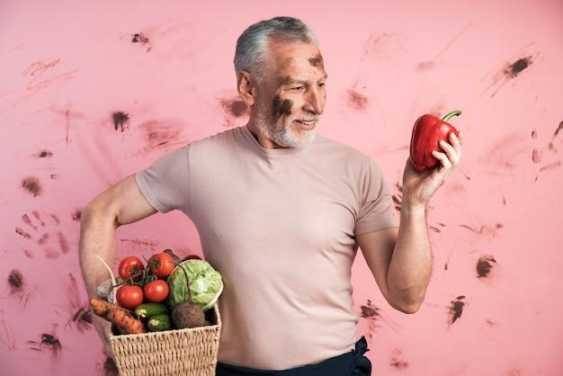 매력적이고 노인은 야채 바구니를 들고 다른 손에는 고추를 들고 있습니다.