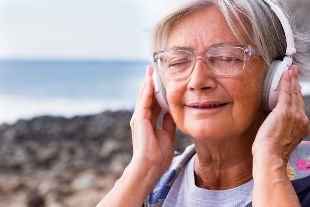 魅力的な年上の女性は、岩の多いビーチに座って白いヘッドフォンと目を閉じて音楽を聴きます。水上の地平線