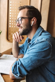 Attractive optimistic man wearing glasses writing and using earpod while working in cafe indoors