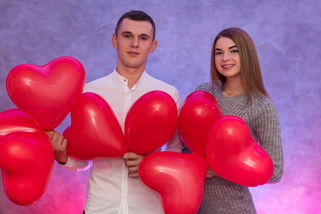 스튜디오에서 웃는 빨간 공기 풍선과 함께 매력적인 쌍. 사랑에 빠진 커플
