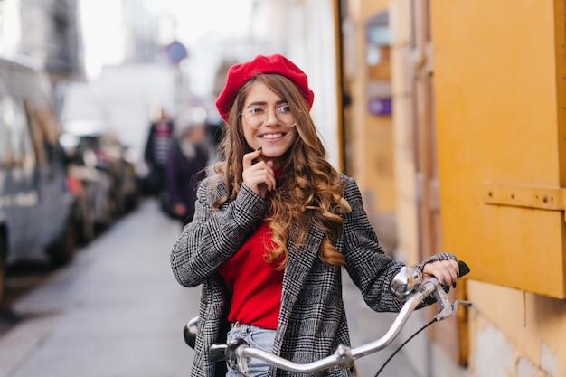 Attraente ragazza pallida in bicchieri ad esplorare la città in bicicletta