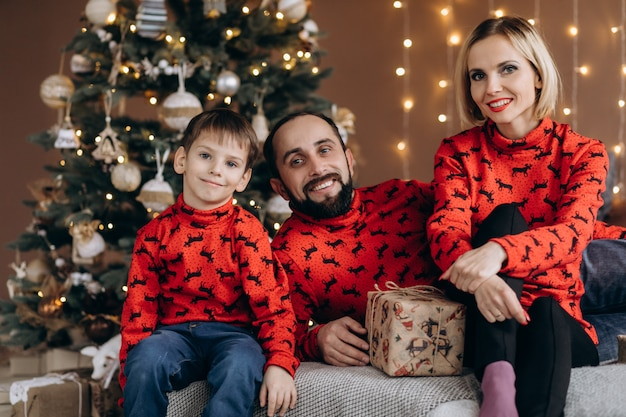 Attractive parents and their little son in red sweaters have fun opening presents before a christmas