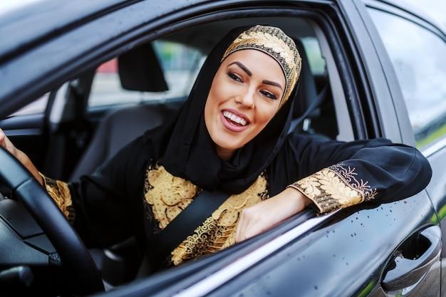Привлекательный пациент улыбается молодая мусульманская женщина, сидящая в своей машине и ожидающая в пробке.