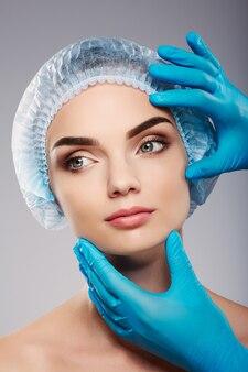 Привлекательный пациент с обнаженным макияжем на фоне студии, руки врача в синих перчатках возле лица пациента, концепция красоты, глядя влево.
