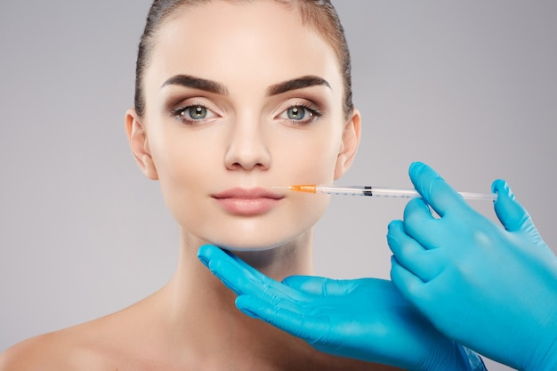 Attractive patient with nude make up at studio background, doctor's hands wearing blue gloves near patient's face, holding syringe with botex near face, beauty concept.
