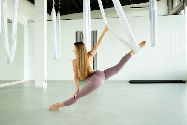 Attractive peaceful young girl doing aerial yoga in studio antigravity