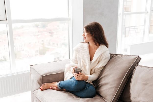 커피 한 잔을 들고 집에서 소파에 앉아 꿈꾸는 매력적인 평화로운 젊은 여성