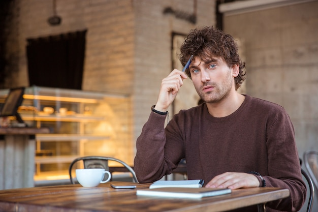 Attractive pencive handsome thoughtful curly young male in brown sweetshirt sitting in cafe with notebook and thinking