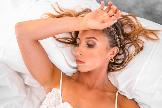 침대에서 잠옷에 매력적인 잠겨있는 금발 백인 젊은 여자