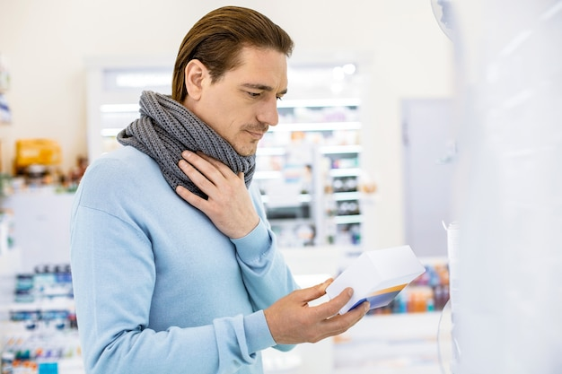 Attractive pensive man touching neck while choosing medication for relieving sore throat